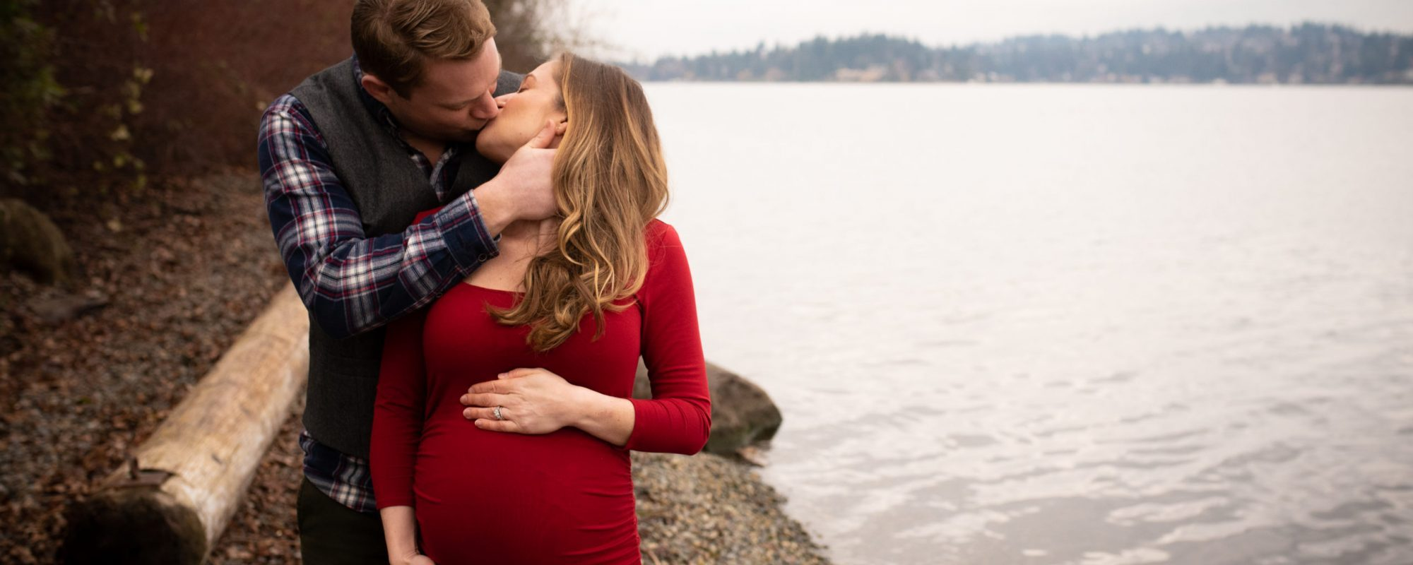 Husband and expecting wife passionately kissing beside a lake.