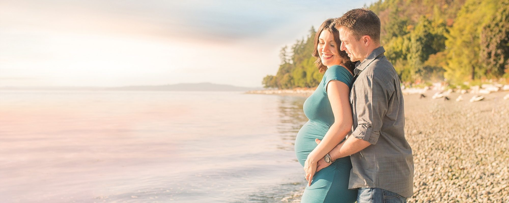Pregnant wife and husband joyfully standing beside a lake.