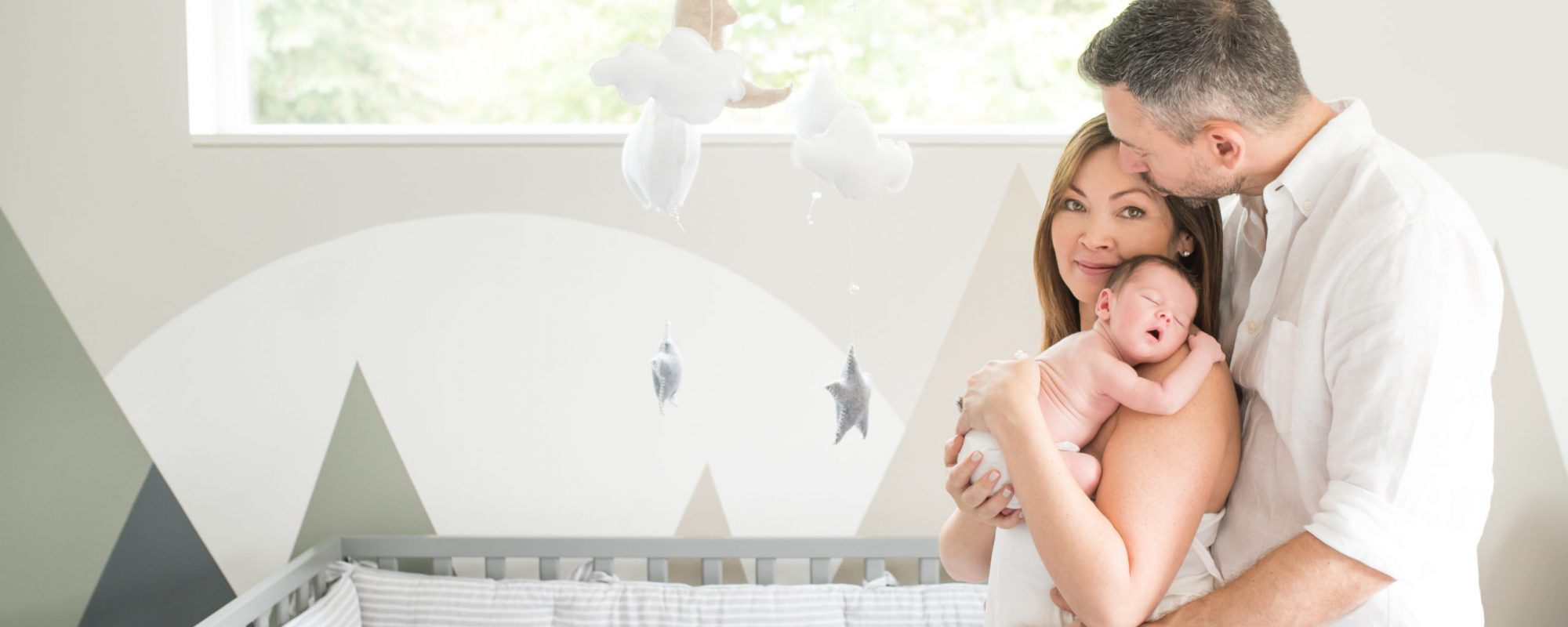 Peaceful couple cradling their newborn in the baby's room.